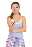 Smiling Young woman in pajamas holding TV remote control