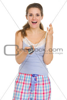 Surprised young woman in pajamas with TV remote control
