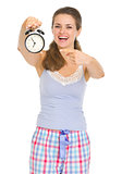 Happy young woman in pajamas pointing on alarm clock