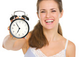 Closeup on alarm clock in hand of happy woman