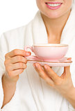Closeup on woman in bathrobe with cup of coffee