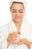 Young woman in bathrobe holding glass with water