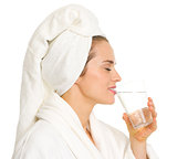 Young woman in bathrobe drinking water