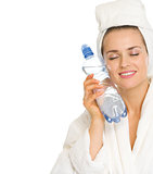 Young woman in bathrobe holding bottle with water
