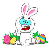 Easter bunny sitting in a patch smiling with Easter eggs