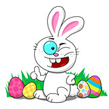 Easter bunny sitting in a patch winking with Easter eggs