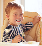 Two year old boy smiles and eating porridge.