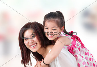 Asian family piggyback ride at home.