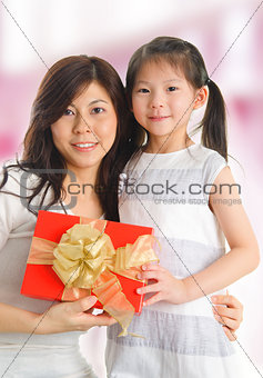 Asian girl giving a gift to her happy mother
