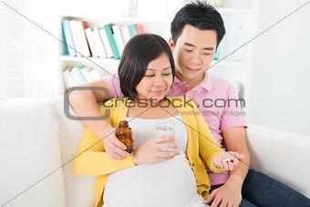 Asian pregnant woman having medicine at home