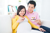 Asian pregnant woman eating cake 