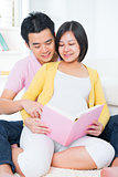 Asian pregnant couple reading book