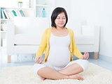 Asian pregnant woman meditating