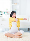 Pregnant woman yoga at home.
