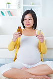 Pregnant woman taking supplements at home.