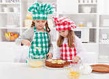 Little girls with chef hats preparing a cake