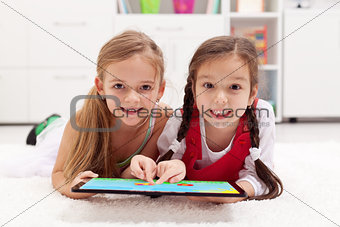 Little girls using tablet computer as artboard