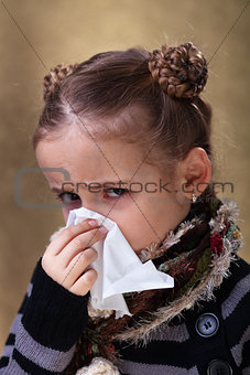 Little girl in flu season - blowing nose