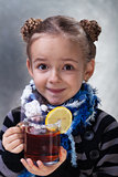 Little girl with large cup of tea
