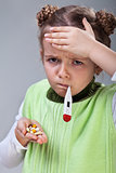 Sick little girl with pills and thermometer