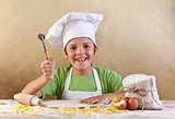 Happy kid with chef hat making pasta or cookie