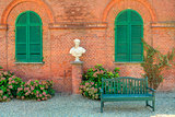 Wooden bench in front of red brick house in Italy.
