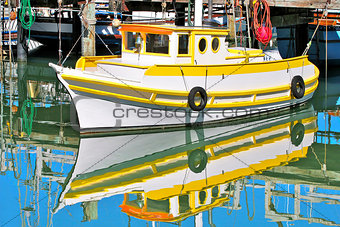 Fishing boat reflected in the water in San Francisco, USA.