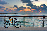 Bike on promenade against background of sunset sky and sea.