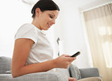 Young woman sitting on couch and writing sms