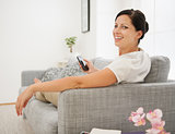 Happy young woman sitting on couch and holding cell phone