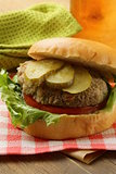 burger with tomatoes and pickled cucumbers on a wooden table