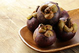 fresh exotic fruit mangosteen on a wooden plate