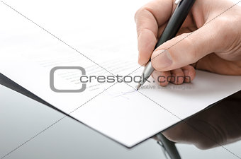 Male hand signing a contract on a black table