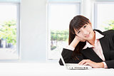 smiling young businesswoman with laptop in the office