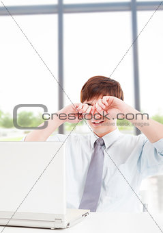 Young businessman with tired eyes and working in office