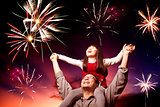 father and daughter looking fireworks in the evening sky