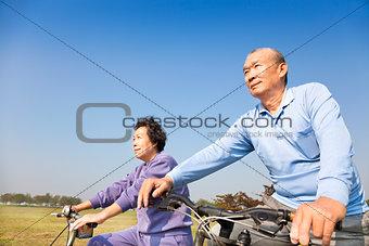 Happy elderly seniors couple biking
