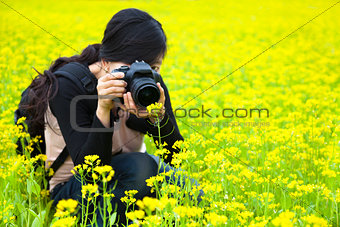 young woman photographer taking pictures in nature