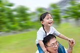 Happy family man running with daughter on his shoulders