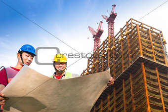two construction workers with giant cranes and building