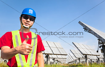 happy worker with thumb up and standing before solar panel track