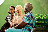 Group of elderly black and caucasian women talking in park