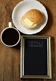 Coffee cup and bun with butter with  slate chalk board