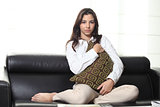 Beautiful teenager on a couch at home hugging a cushion