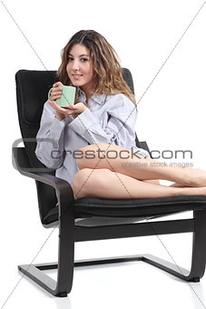 Beautiful woman just woke up holding a cup on an armchair