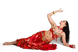 Beautiful young girl in a red suit oriental dance in motion isol