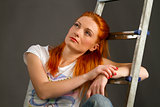 Beautiful young red-haired girl leaning on a ladder