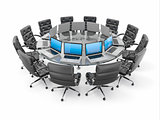 Conference table with laptops and armchairs