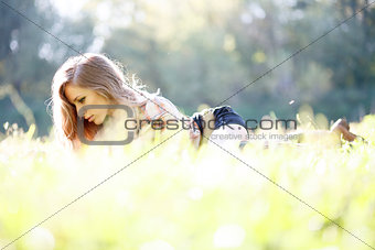 Beautiful Young Woman lying on grass reading
