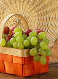 Red and green grapes in a wicker basket